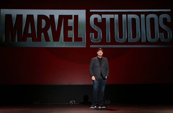 Kevin Feige on stage with the Marvel Studios logo behind him