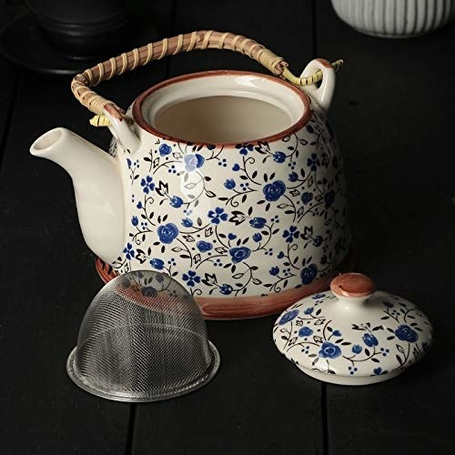 A white ceramic teapot with a blue floral design