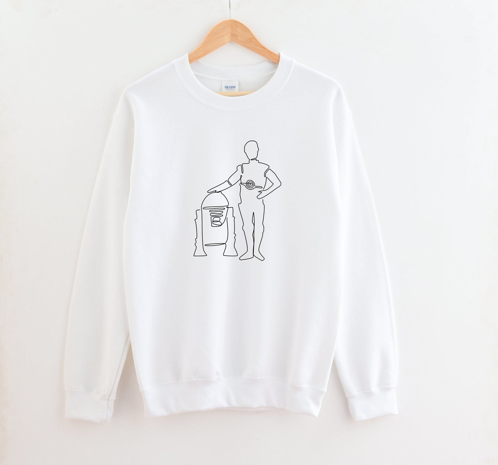 a white sweatshirt with outlined drawings of the two droids on it