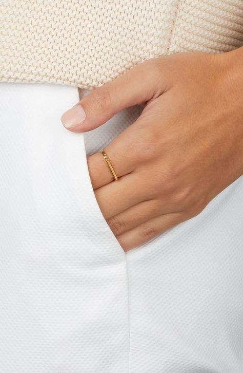 model wearing the ring with half of hand in pocket