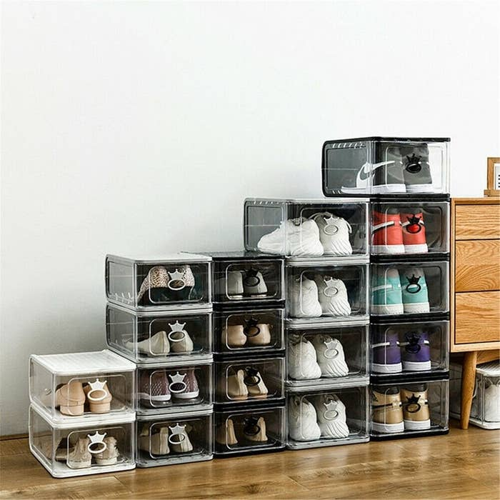 Several pairs of shoes, each inside the stackable boxes. The shoes can be see through the clear plastic drawers.