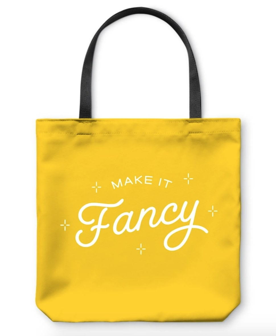 """Yellow tote bag with black handle and """"Make It Fancy"""" logo in white"""