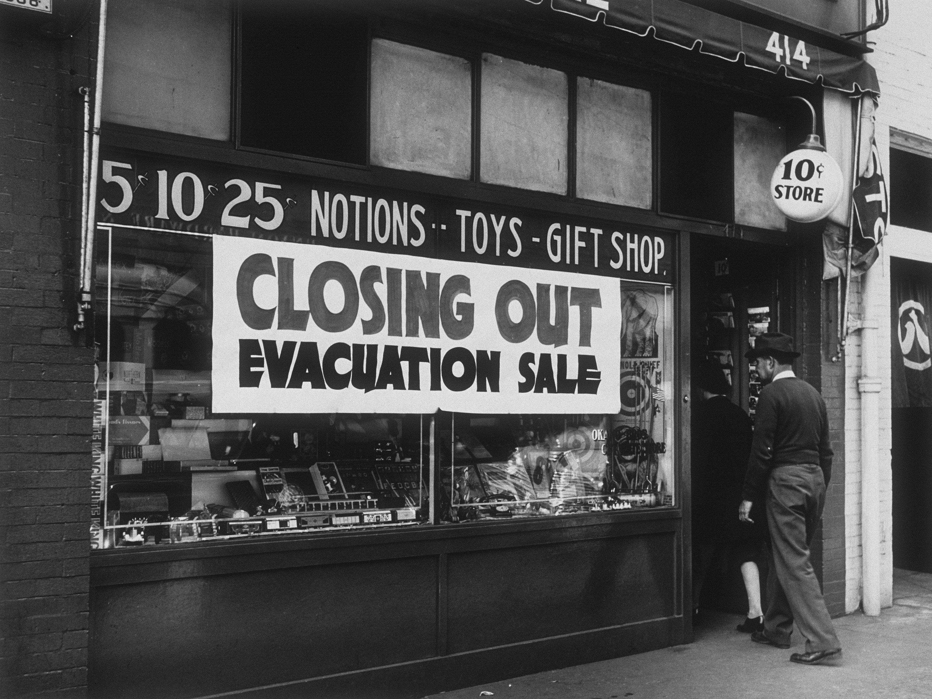 """A sign on the store says """"Closing Out Evacuation Sale"""""""