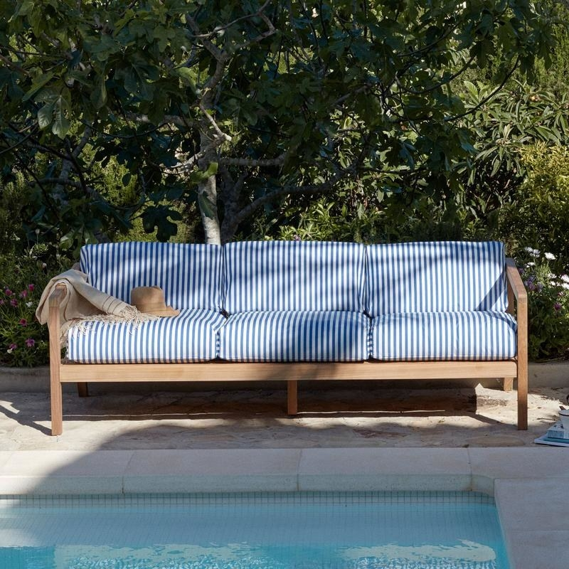 teak sofa by pool, with blue and white striped cushions