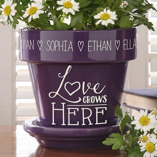"purple flower pot that says ""love grows here"" and lists custom names around the top rim"