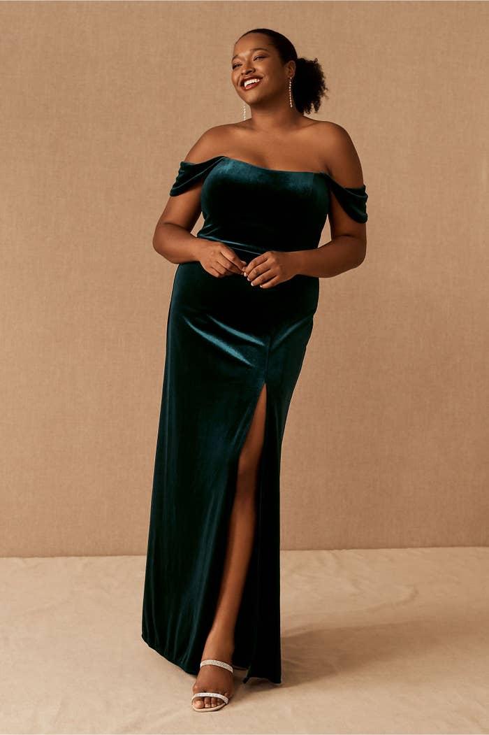 model wearing emerald green velvet off-shoulder gown