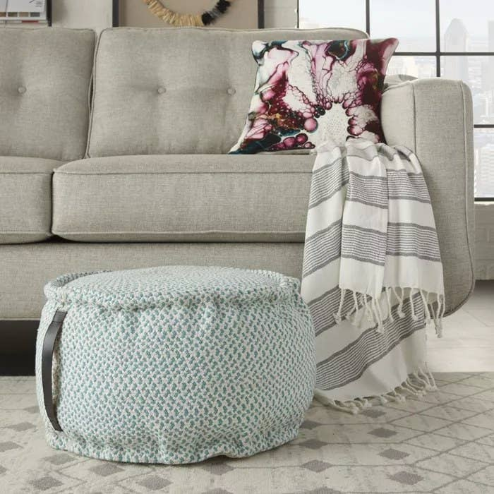 The turquoise pouf with a leather handle
