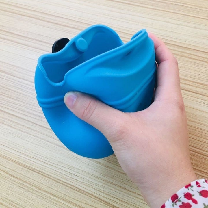 a reviewer photo of a hand squeezing the sides of the pouch to open it