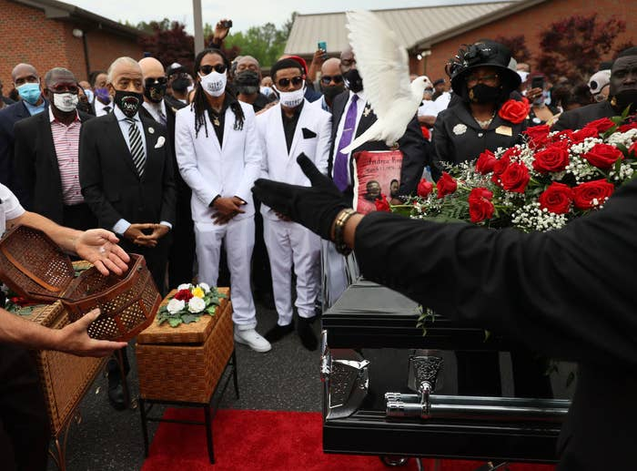 Black men wearing suits and face masks stand around a casket at a funeral service