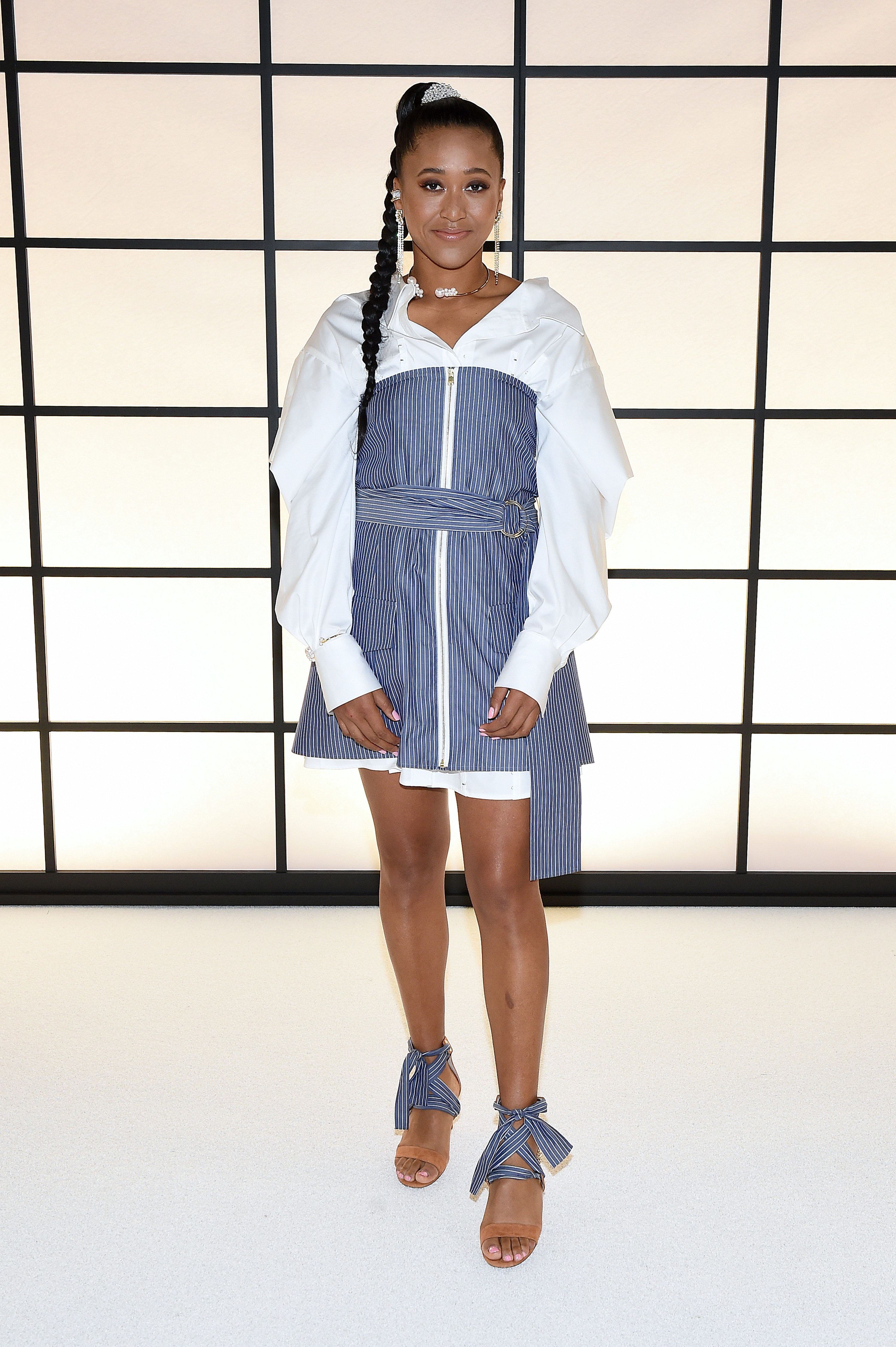 Naomi wears a blue striped dress on top of a white button-up