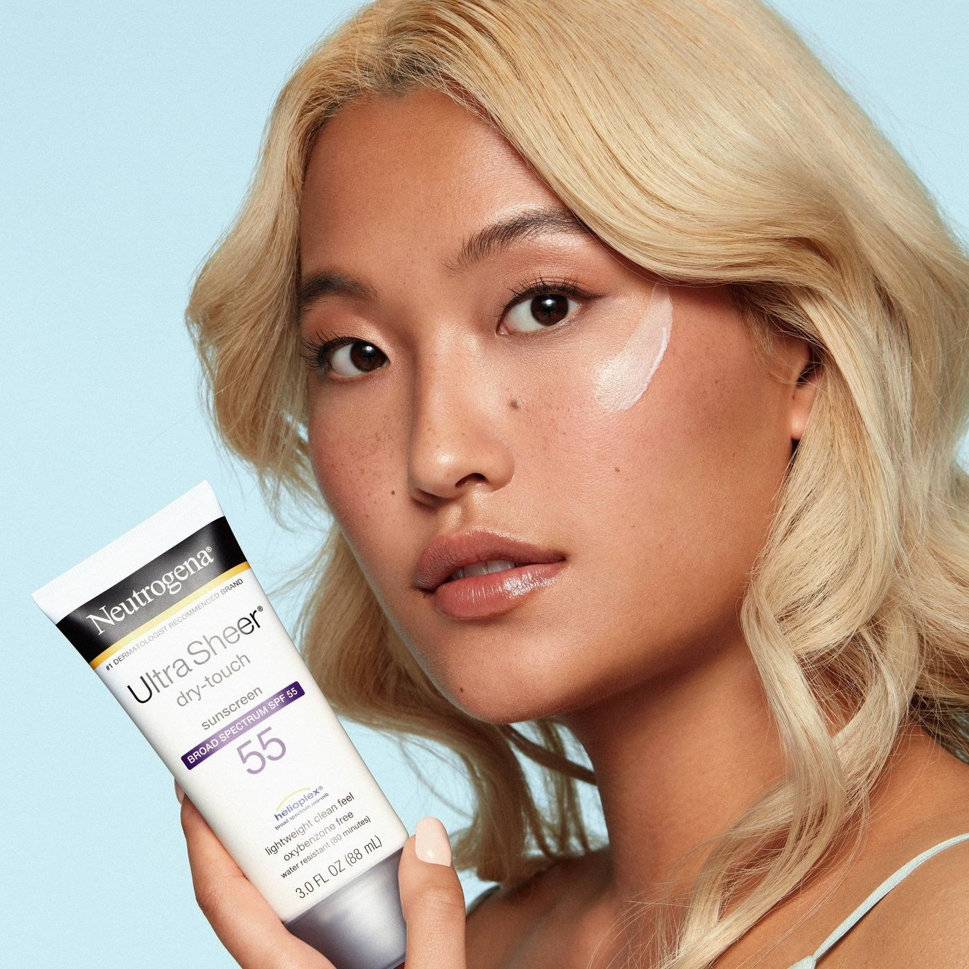 model uses white, black and purple bottle of sunscreen