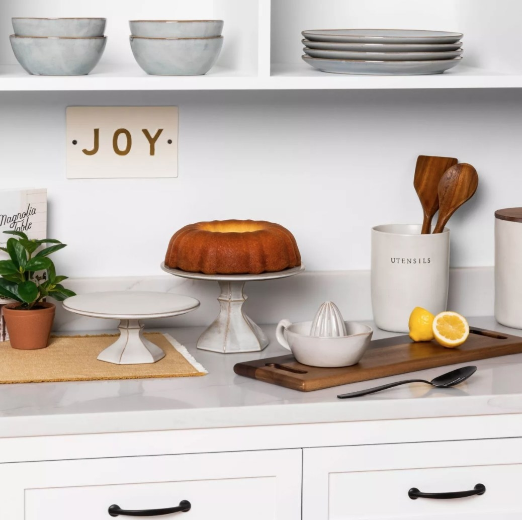 """A white stoneware countertop utensil holder that has """"utensils"""" printed on the front"""