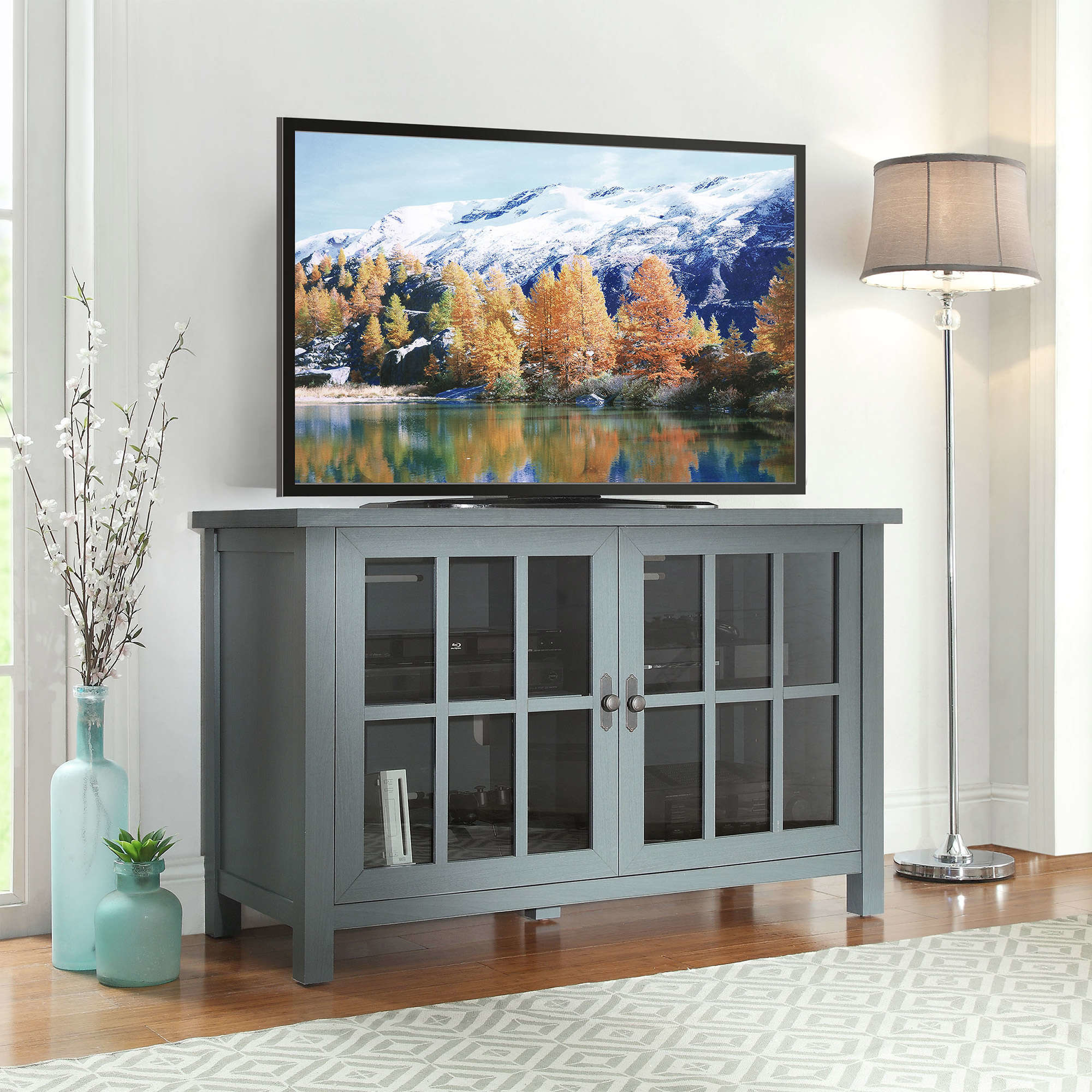 a blue TV stand with glass front cabinet doors