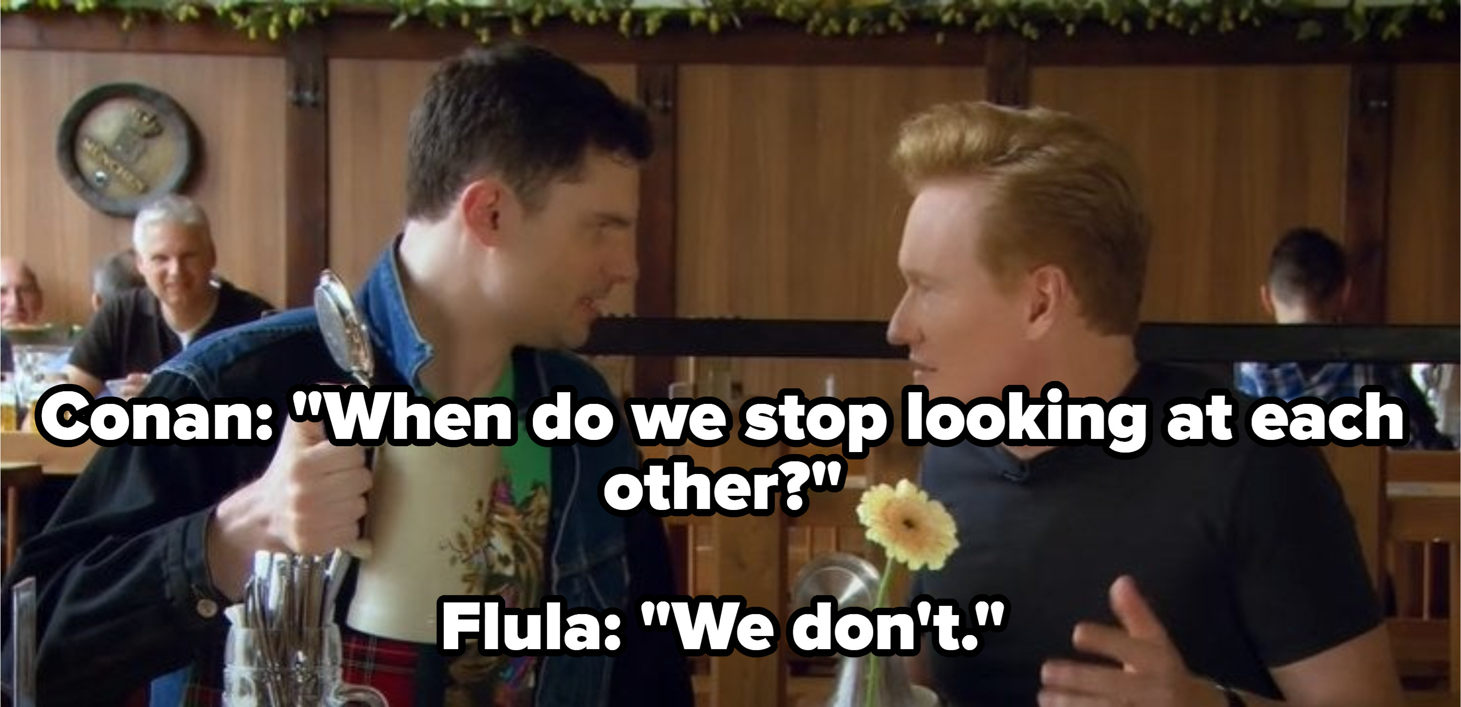 Conan and Flula Borg staring at each other with pints of beer