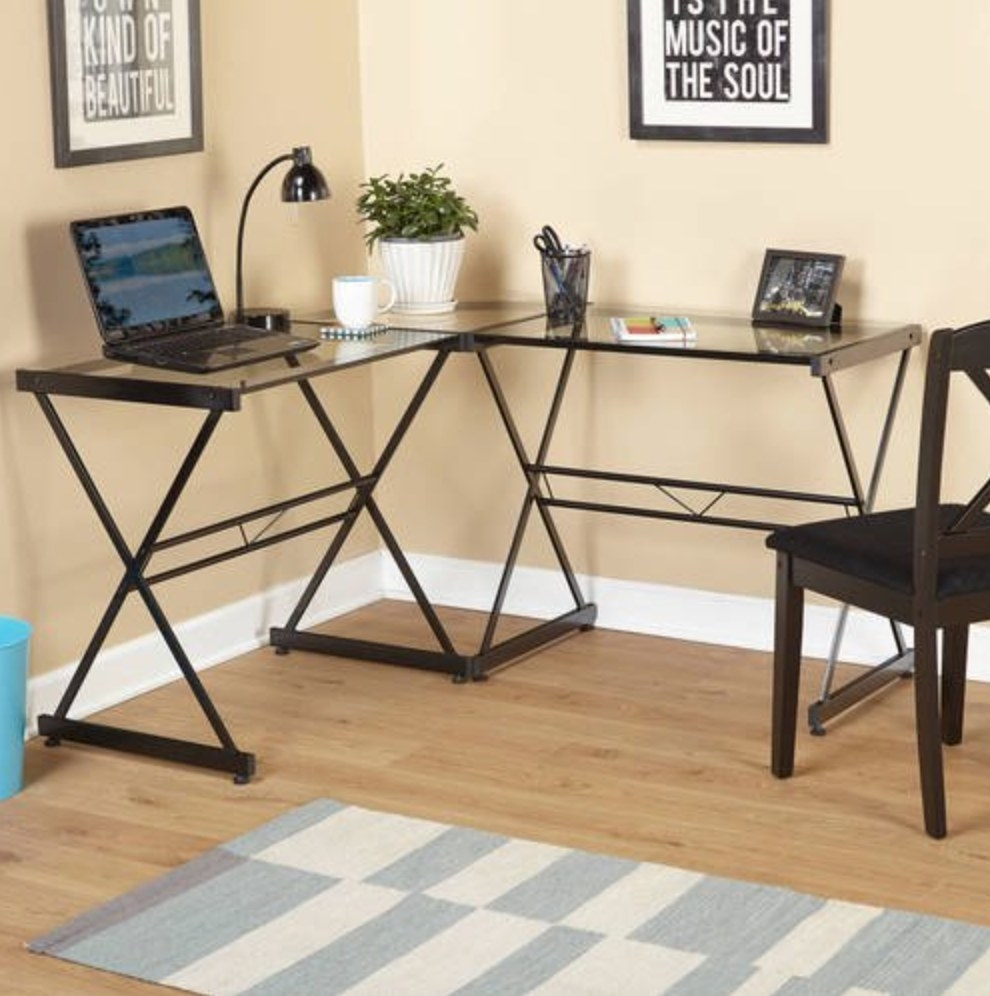 L shaped desk with black metal frame and glass surface