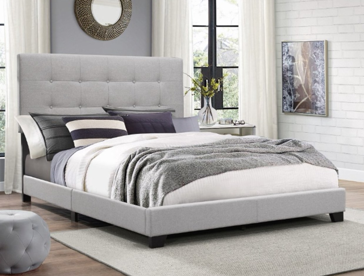 a gray upholstered bedframe with tufted headboard