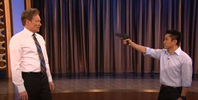 Man points a gun at Conan