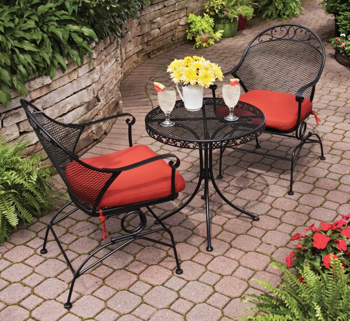 two chairs and a small table in black metal with red seat cushions