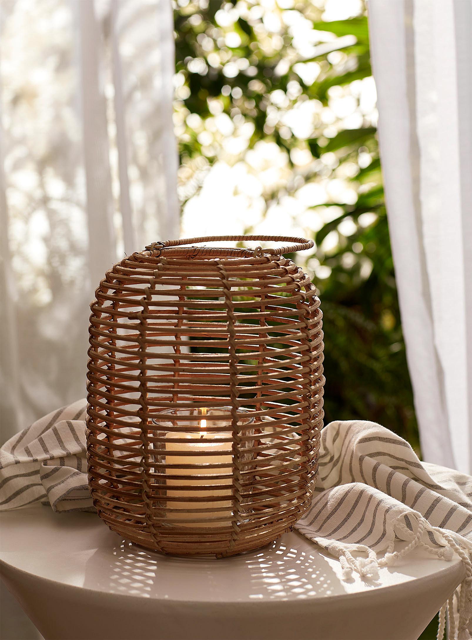 A burning candle inside a rattan lantern