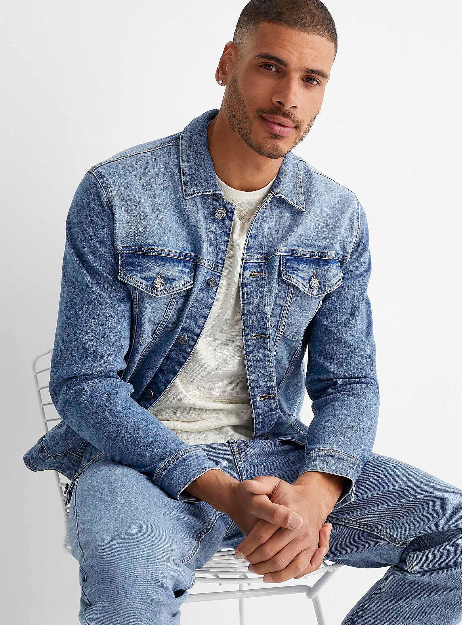A person wearing a denim jacket over a plain shirt and jeans