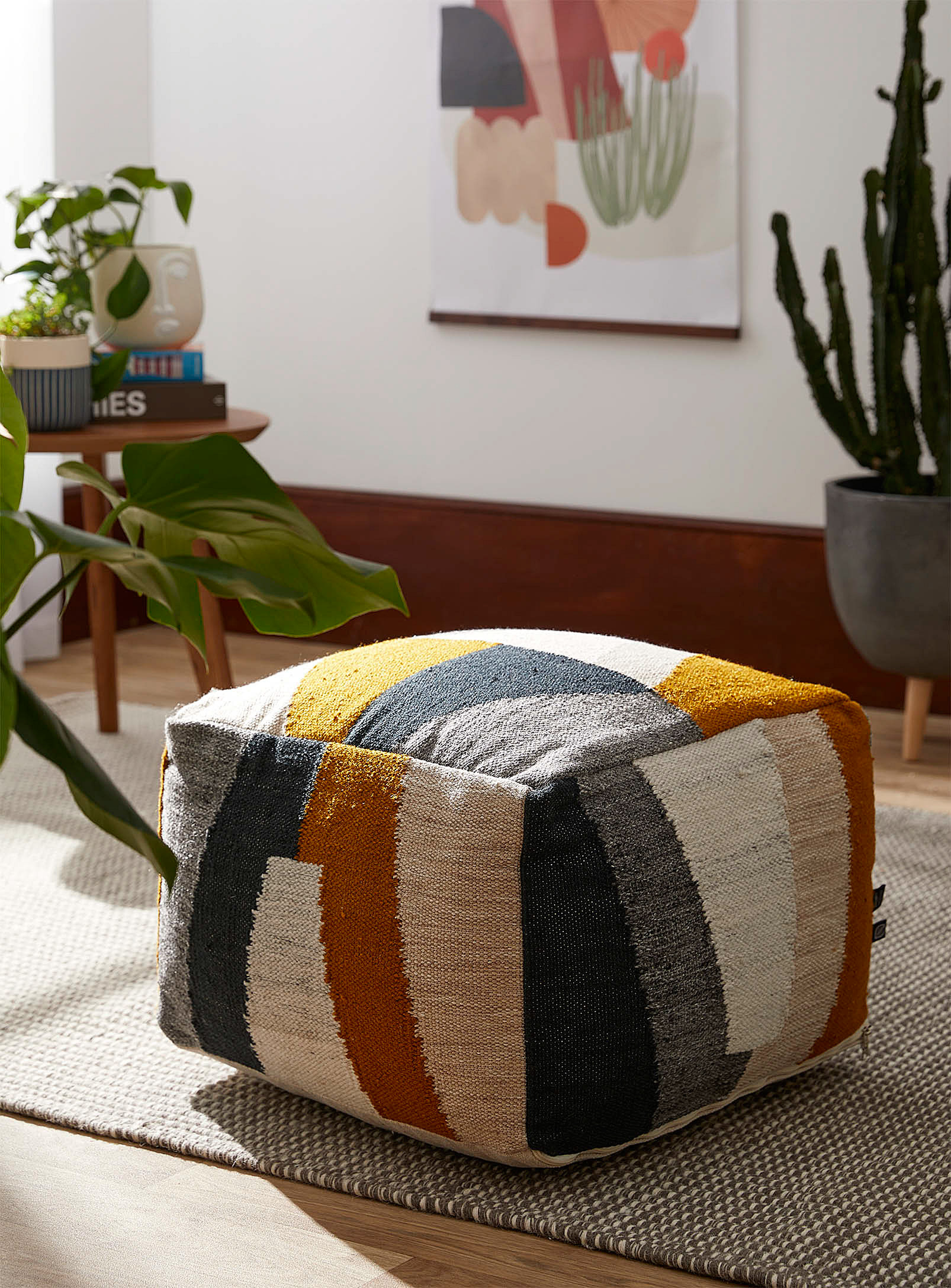 A large square-shaped ottoman on a carpet in a living room