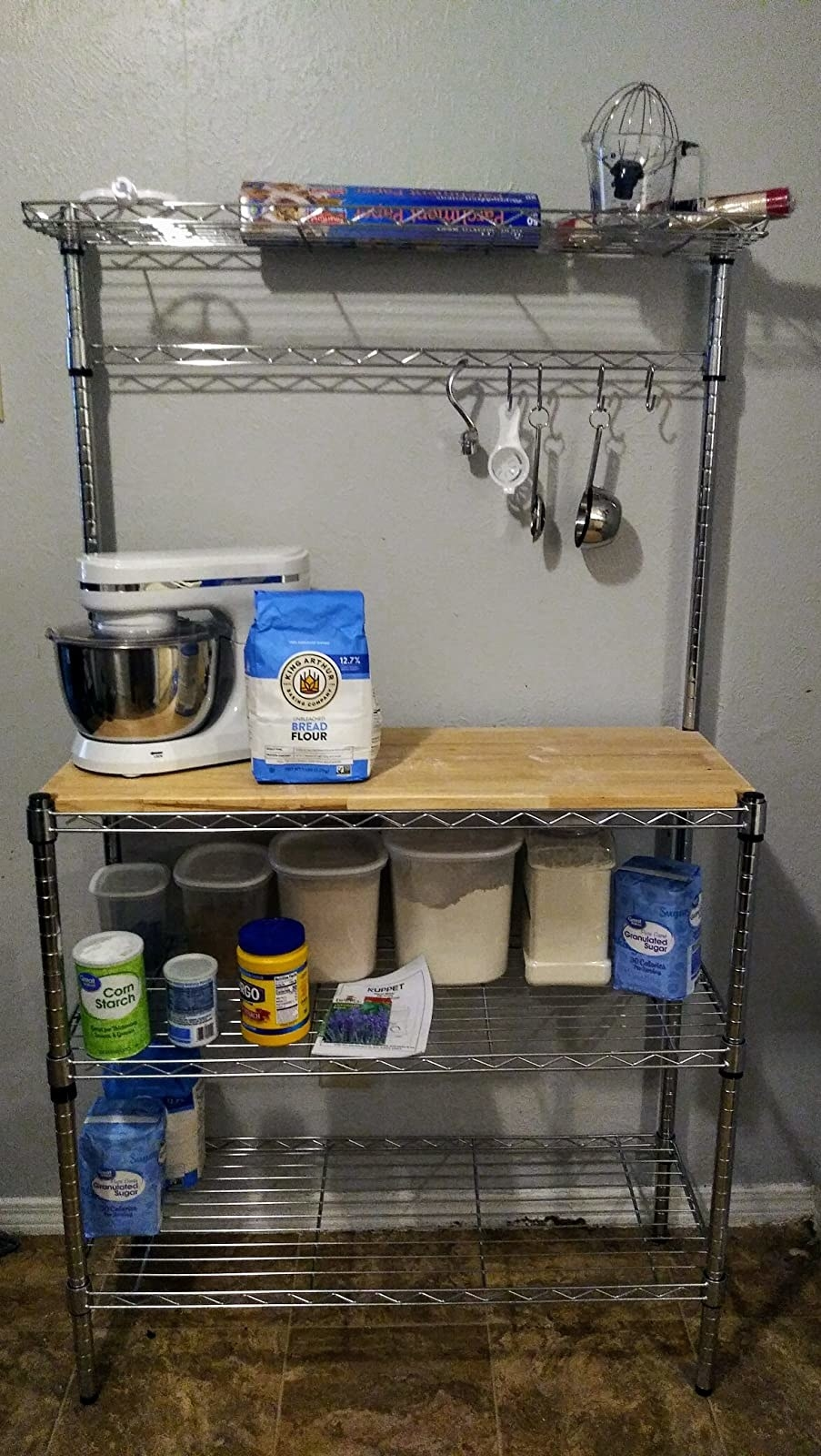 A reviewer photo of the baker's rack, which has four shelves and hanging S-hooks