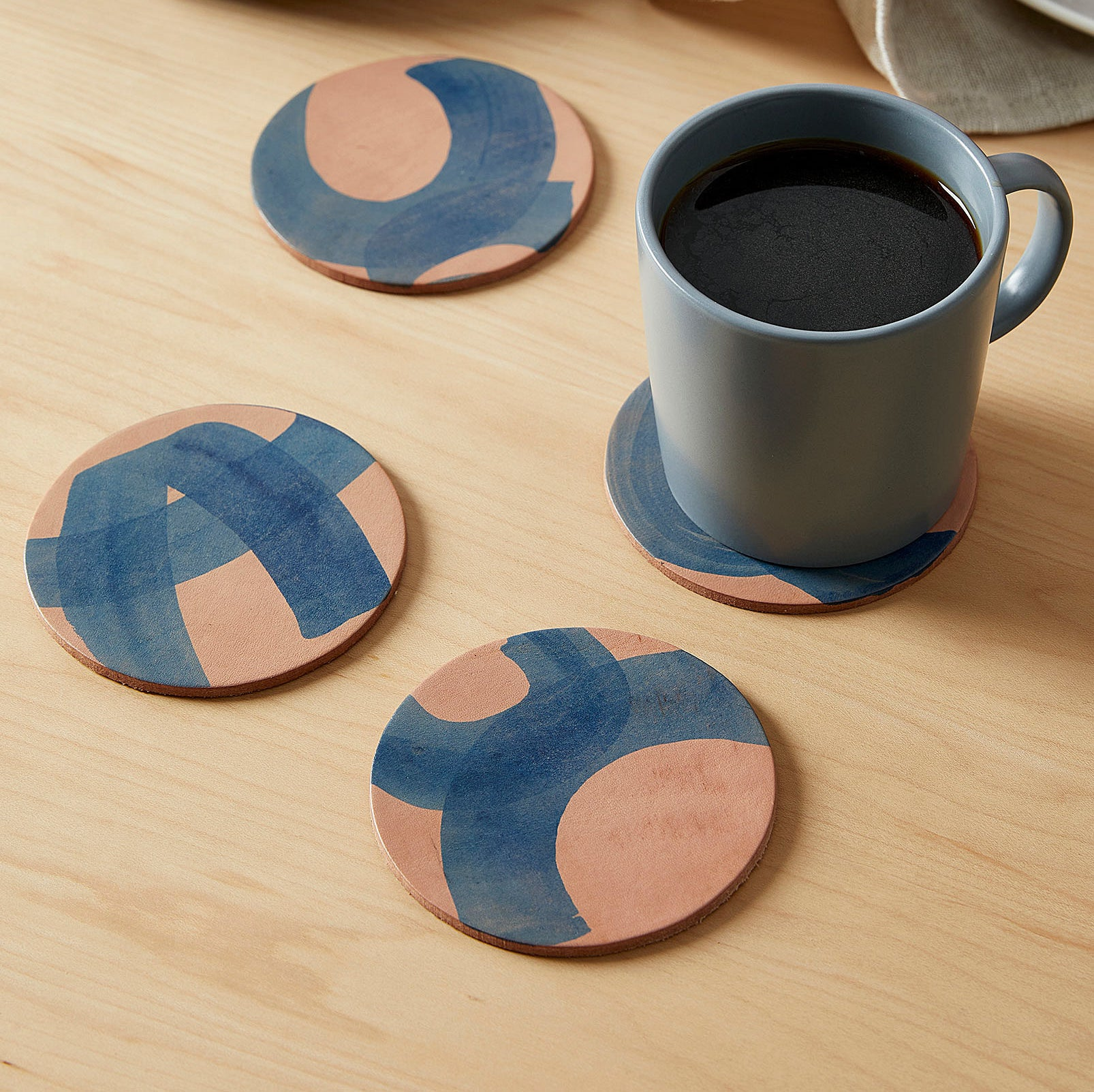 Four coasters with a cup of coffee on one of them