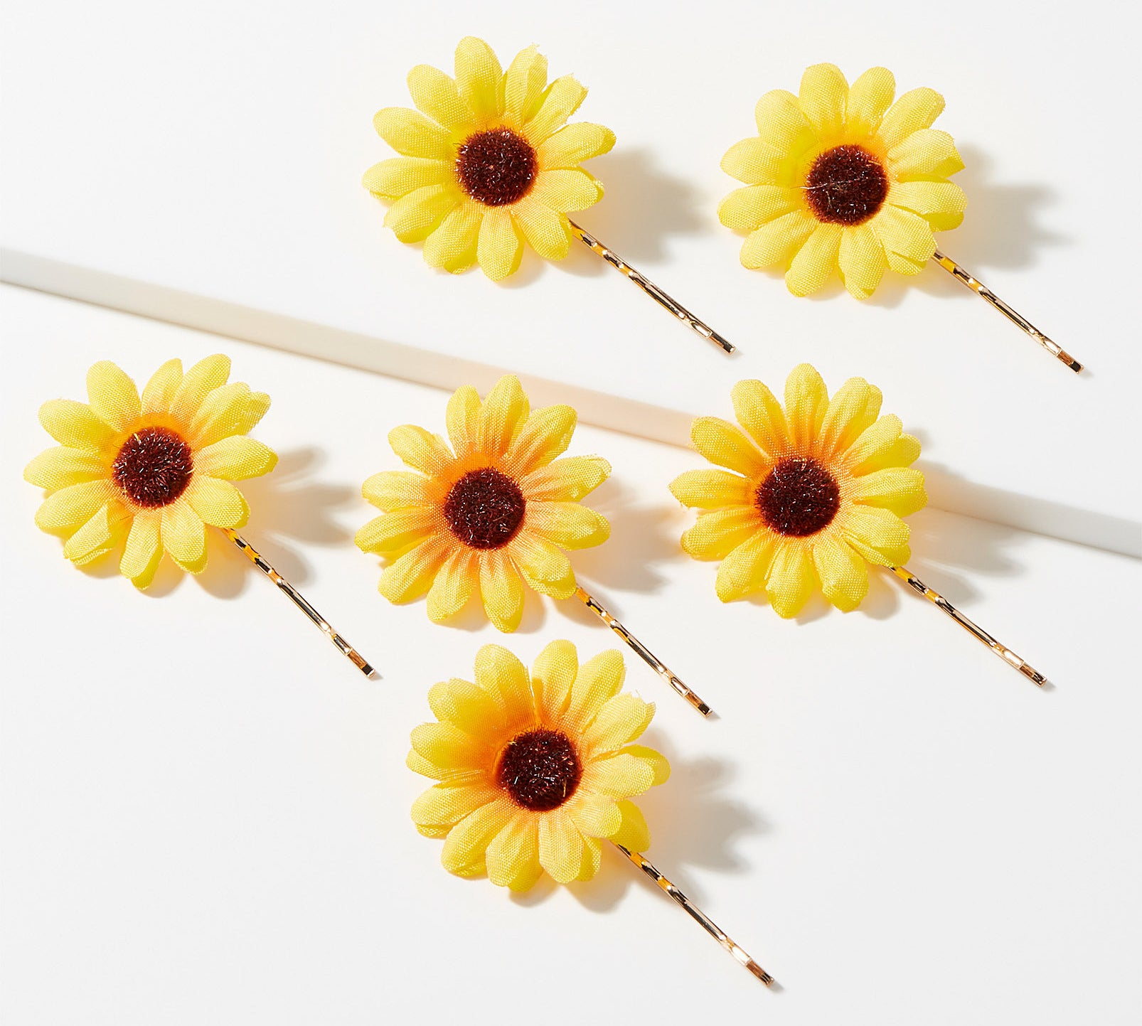 six bobby pins with flowers attached to the ends