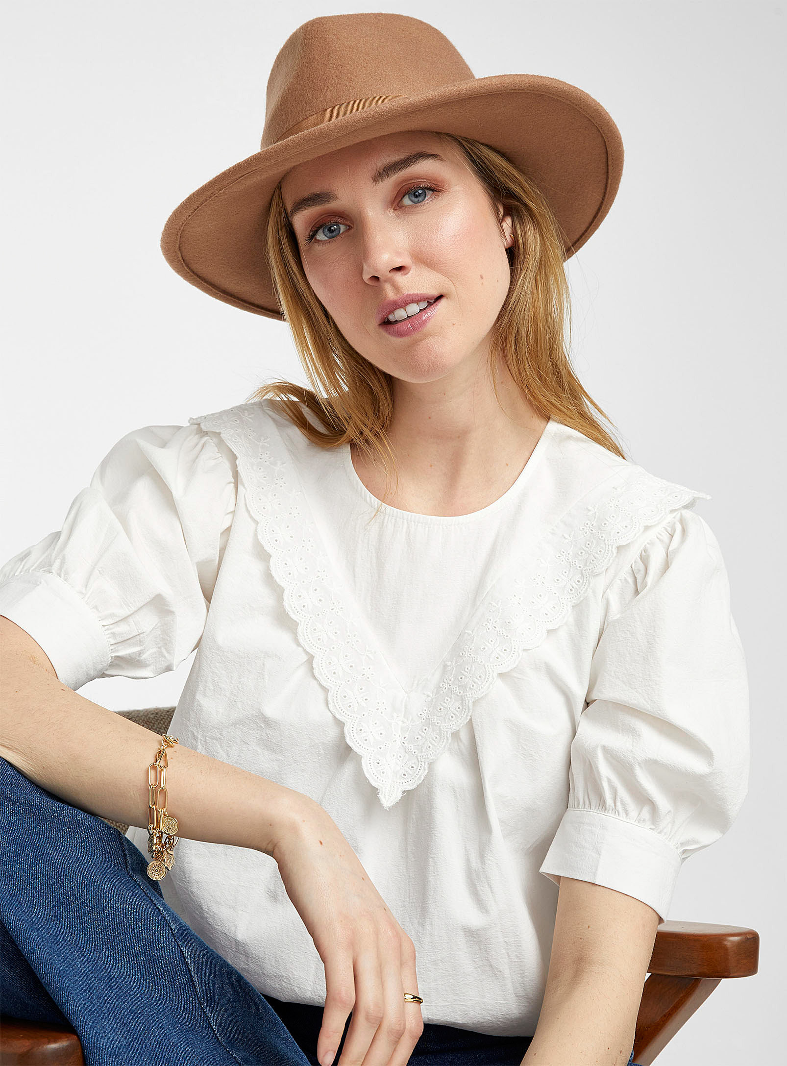A person wearing a blouse with jeans
