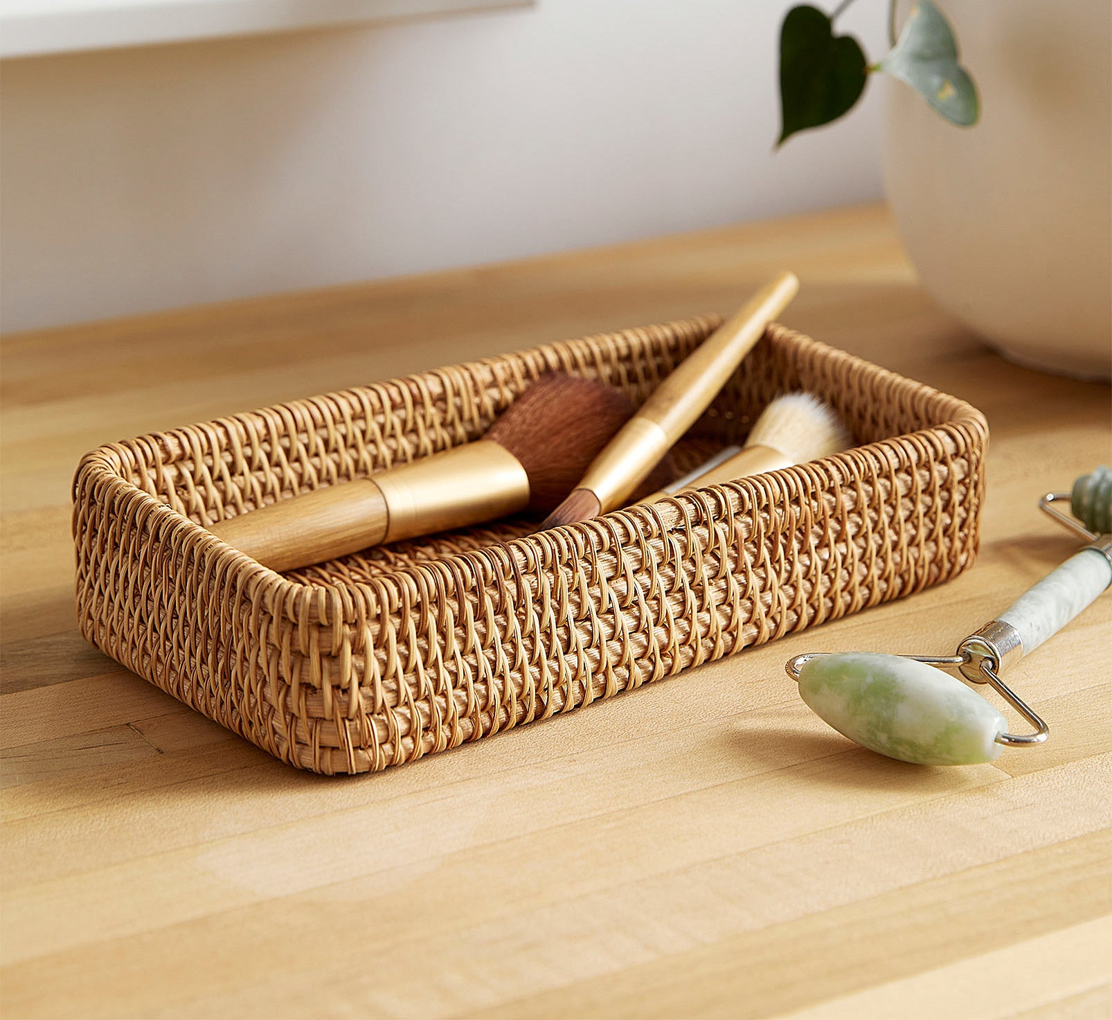 A small basket with three makeup brushes