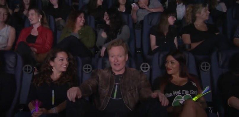 Conan sitting in a movie theatre full of women
