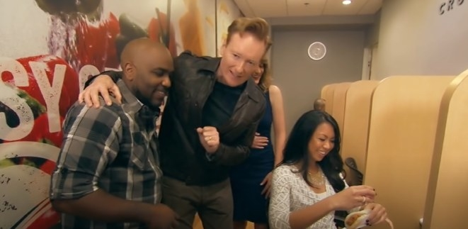 Conan and employee watching woman pour sauce on taco