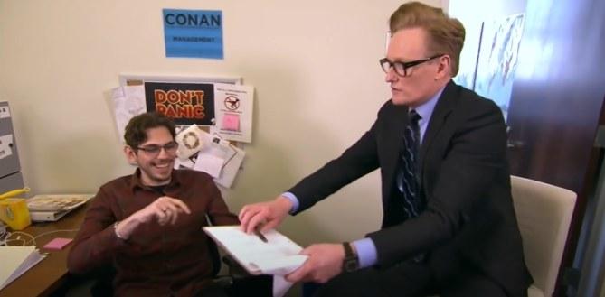 Conan handing clipboard to employee