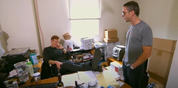 Jordan Schlansky looks at Conan sitting at his desk