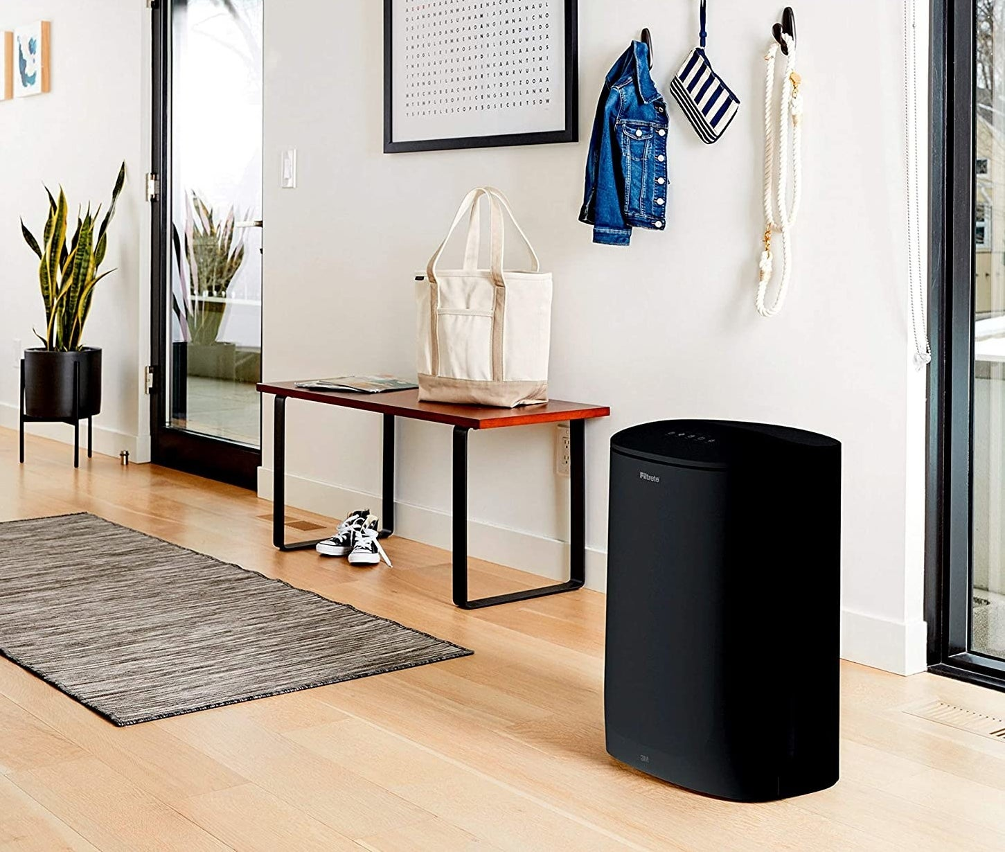 black air purifier styled in an entryway
