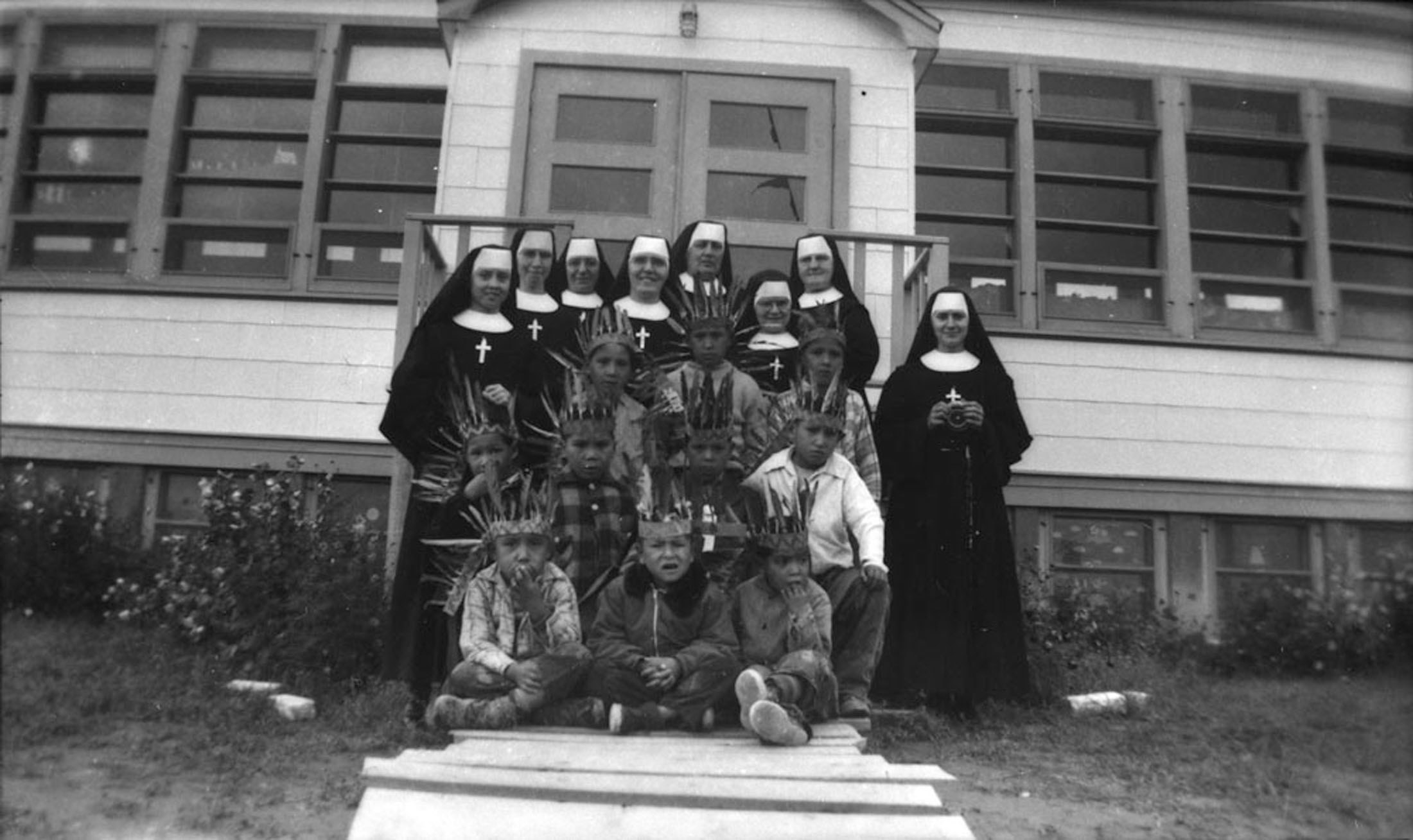 A group of nuns stand in front of sitting Indigenous children