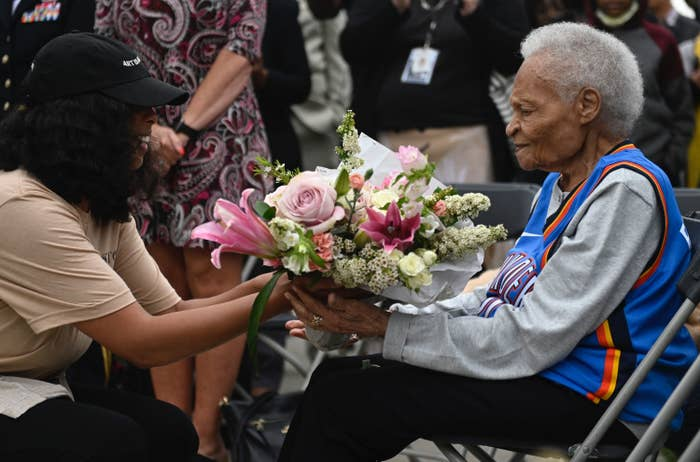 A Black woman in wheelchair receives a bouquet of flowers