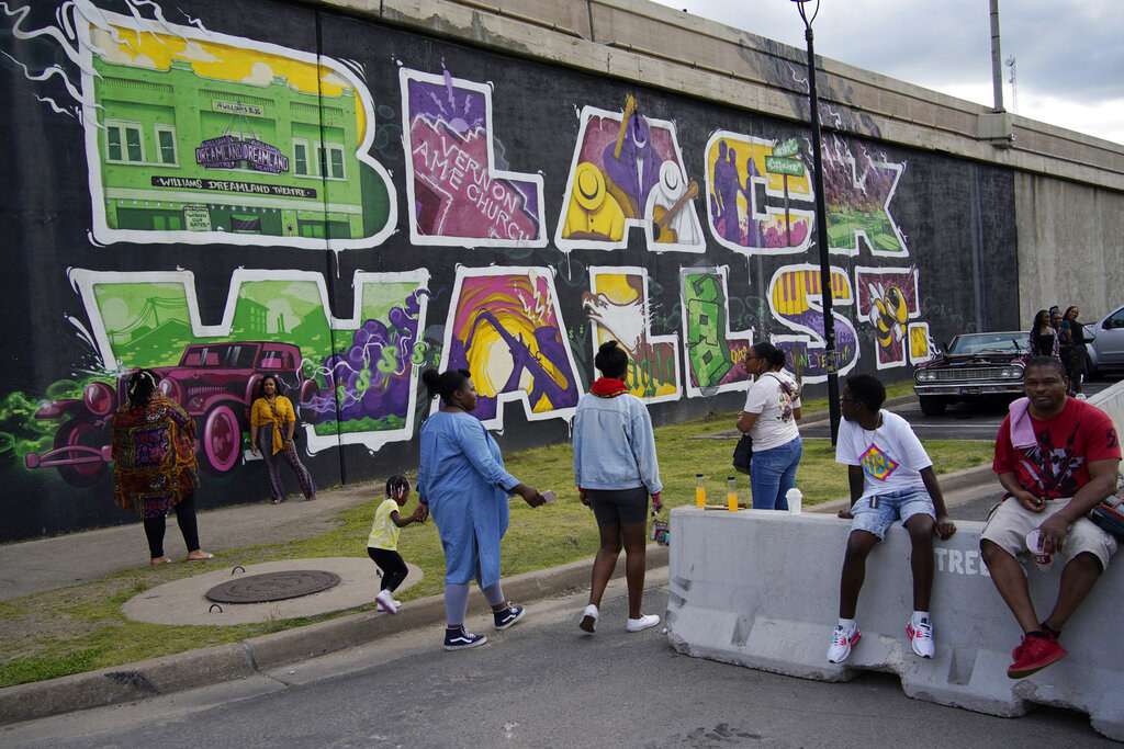 """People walk by a colorful """"Black Wall St."""" mural"""