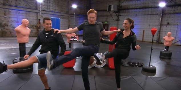 Conan, Gal Gadot, and a trainer high kick in a line