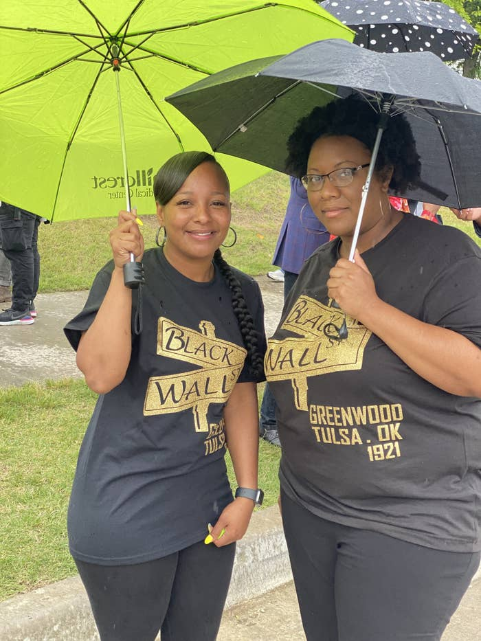 Two women stand together under umbrellas with T-shirts commemorating Black Wall Street