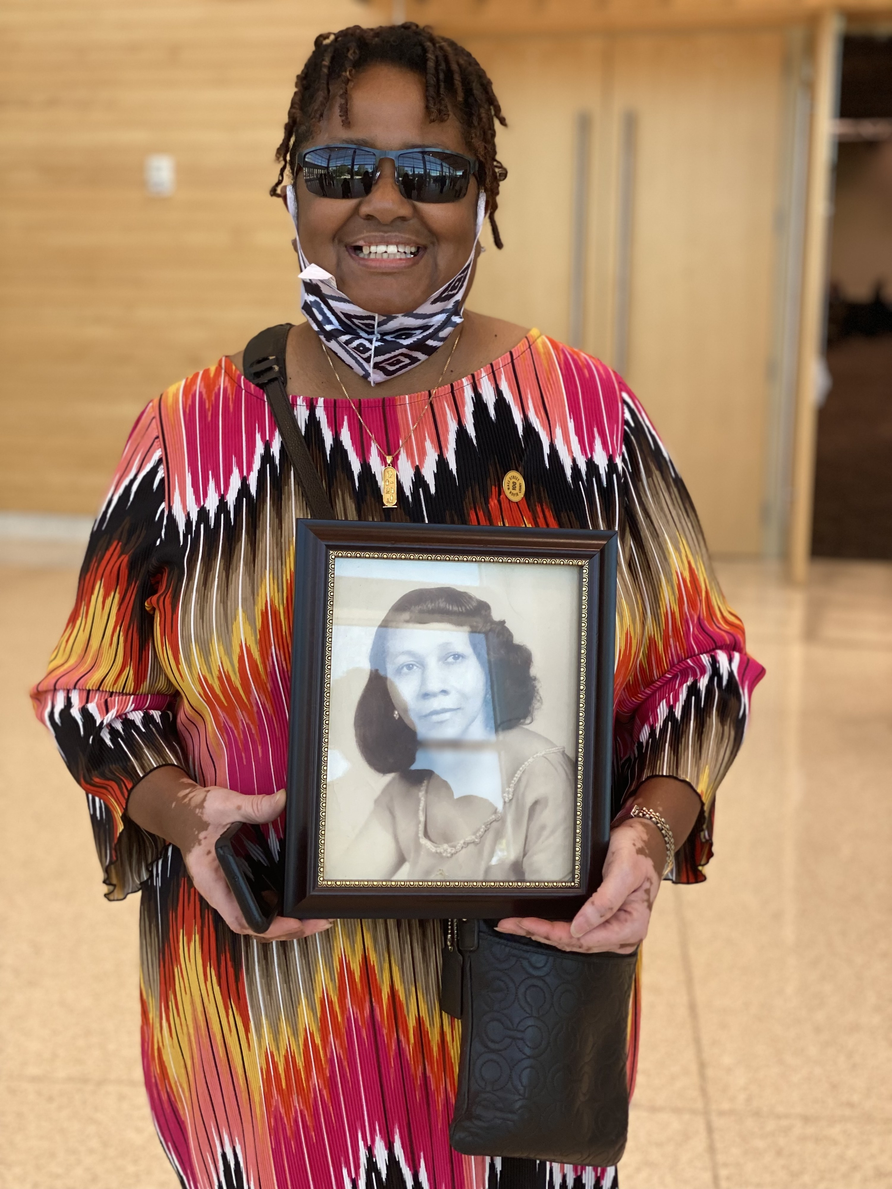A smiling Cherri Lewis stands while holding a framed photo of her grandmother