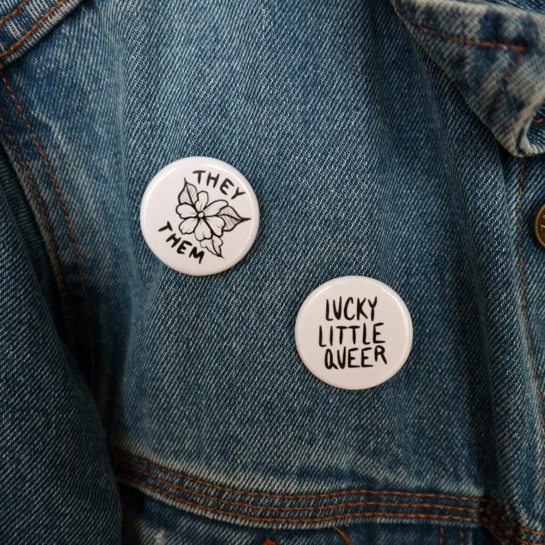 A denim jacket with a pin that says they them on it