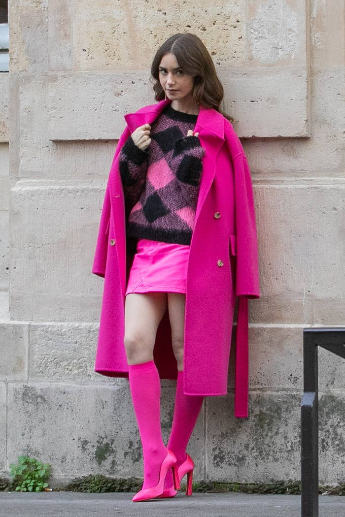 Emily leaning against a wall and wearing a chic pink outfit: coat, sweater, miniskirt, high socks, and high heels