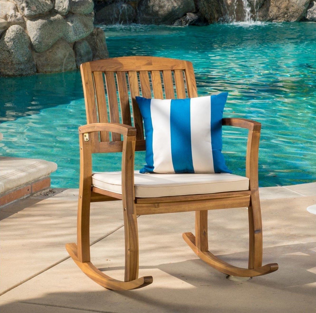 Brown rocking chair with cream cushion and blue and white pillow by an aqua pool
