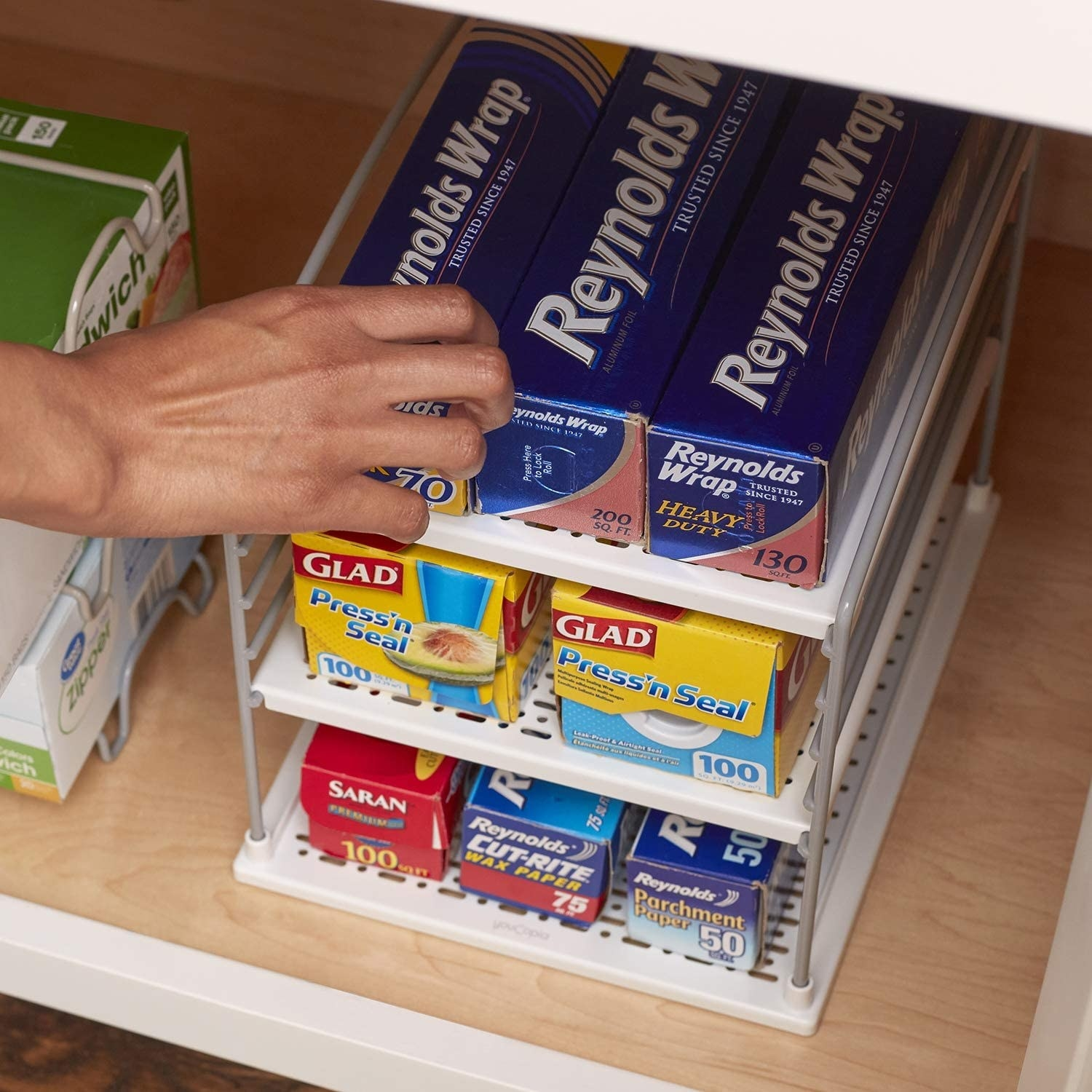 person reaching for a box of food wrap on the organizer