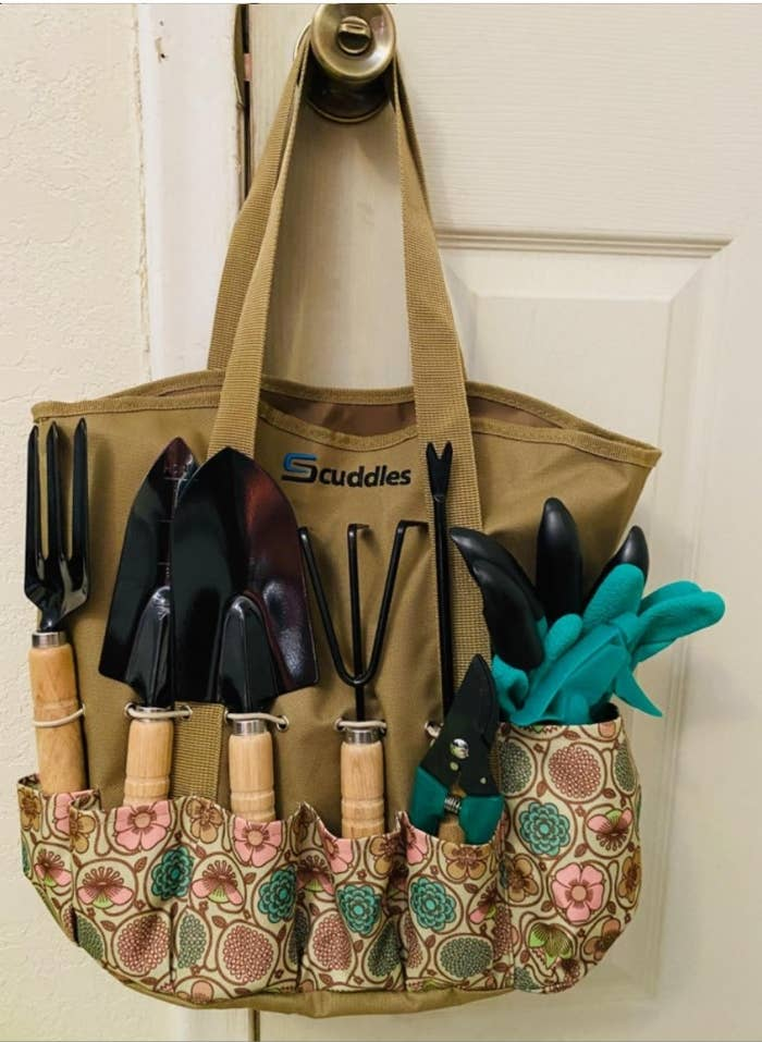 The full gardening tool set in the tote bag hanging on a door