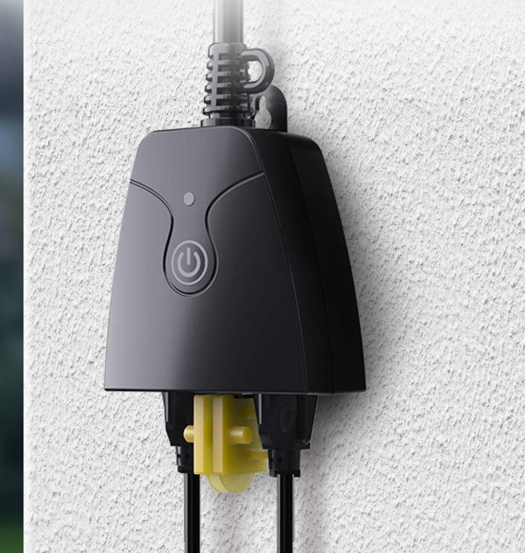 the smart outlet with two sockets hanging against a wall