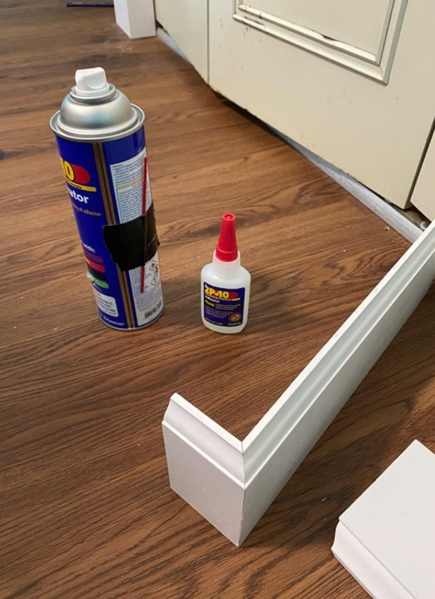The glue bottle and activator sitting beside two boards of wood that have been glued together