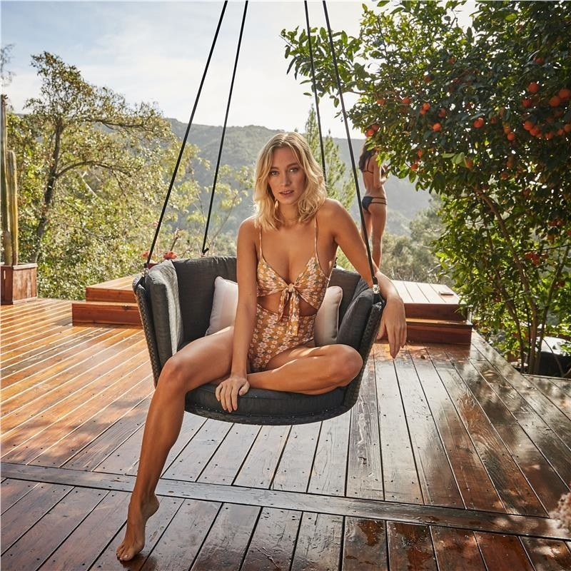 Model sitting in a gray fabric padded round hanging swing on a porch