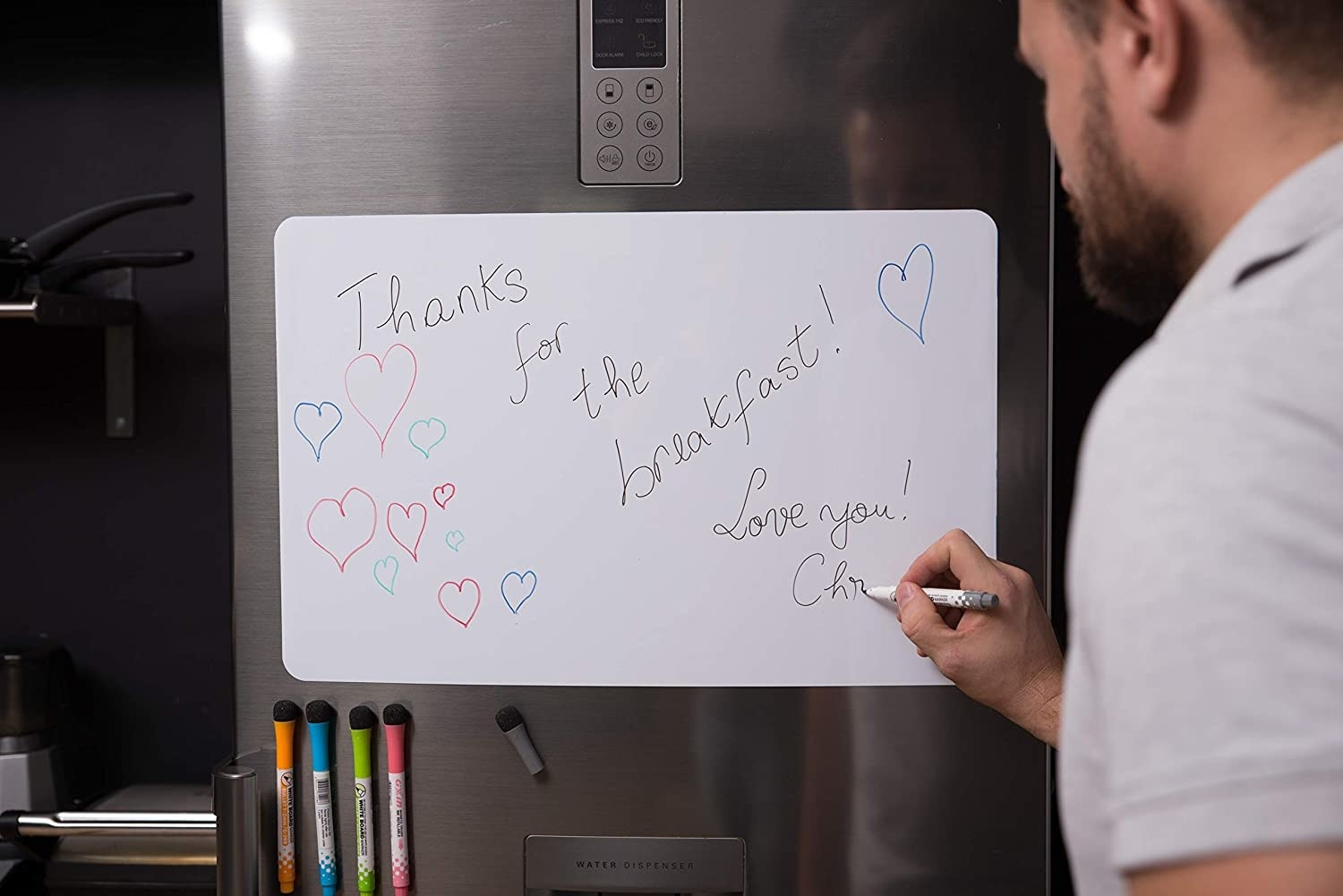 Someone writing on the magnetic whiteboard that's mounted on a fridge